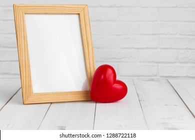 Photo frame and red heart on white wood table with copy sapce, love concept.