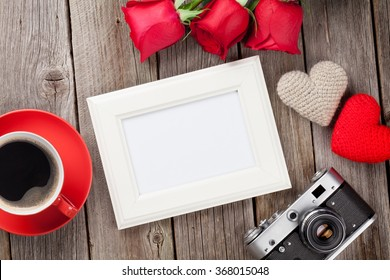 Photo frame, red roses, coffee cup and Valentines day hearts over wooden table. Top view with copy space