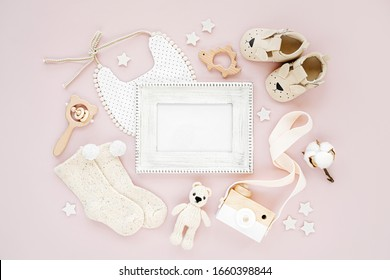 Photo frame with set of clothes and accessories fot newborn girl. Toys, socks and baby slippers with bib on pink background. Mock up tor text. Baby shower concept. Flat lay, top view