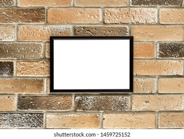 A photo frame with white empty space for text hangs on an old brick wall. Grunge brick wall with a photoframe