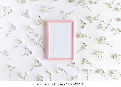 Photo frame with white paper card mockup. Floral pattern made of white gypsophila on a white background