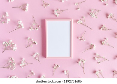 Photo frame with white paper card mockup. Floral pattern made of white gypsophila on a pink pastel background