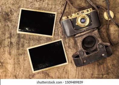 Photo frames and film camera on wooden background. Vintage still life