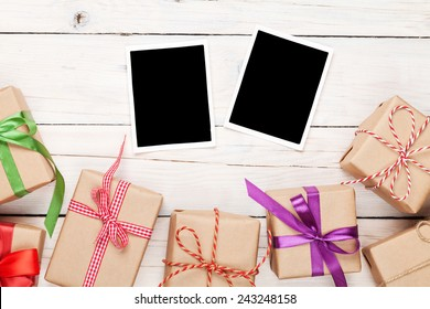 Photo frames and gift boxes with ribbons over white wooden table background