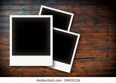 Photo frames on wooden board background texture
