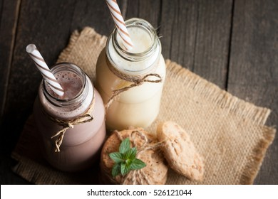Photo of fresh Made Chocolate Banana Smoothie on a wooden table with cookies, banana and coconut. Milkshake. Protein diet. Healthy food concept. Drink, coffee beans, chocolate.