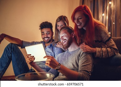 Photo of friends having fun together in the apartment while watching something on a digital tablet.