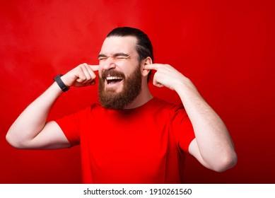 Foto von frustriertem bärtigen Mann, der Ohren mit Fingern auf rotem Hintergrund schließt.