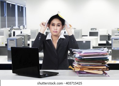 Photo of frustrated female entrepreneur put a paperwork on her head with a pile of document and laptop on desk in office