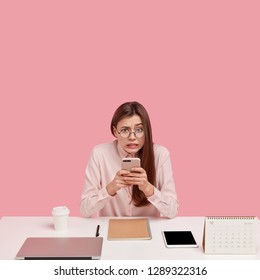 Photo of frustrated woman holds mobile phone, sends money via online bannking app, surrounded with laptop computer, spiral notepad, calendar, isolated over pink background, being perfectionist