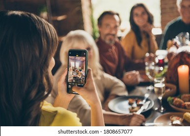 Photo of full family gathering small daughter hold telephone make adorable picture digital camera focusing push button dinner big table turkey generation in home evening living room indoors
