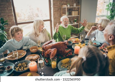 Photo of full family reunion gathering sit feast dishes chicken table communicating fall november autumn holiday multi-generation in evening living room indoors