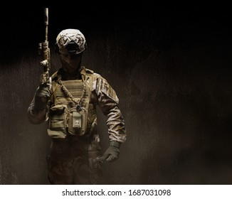 Photo of a fully equipped desert camouflage soldier in mask, helmet, armor and gloves standing with rifle on dark foggy concrete background front view.