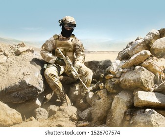 Photo of a fully equipped military soldier with rifle sitting in desert trench.