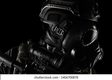 Photo of a fully equipped soldier in black armor tactical vest, gas mask, automatic rifle, gloves and helmet standing on black background closeup profile view.