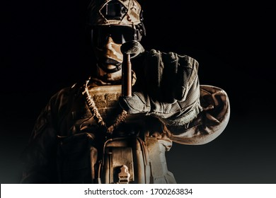 Photo of a fully equipped soldier in desert camouflage outfit holding a bullet shell in gloves on black background.