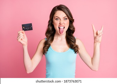 Photo of funky cool lady hold card show rock sign tongue out wear blue top isolated over pastel pink color background