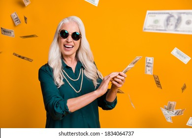 Photo of funky grandma lady hold pack usa bucks money fall from sky wealthy waste money rich person wear green shirt sun specs necklace isolated bright yellow color background