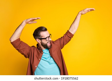 Photo of funky happy cheerful young man raise hands look empty space good mood isolated on yellow color background