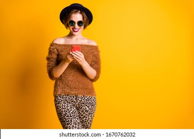 Photo of funky pretty beautiful lady hold telephone hands read new post blog comments wear sweater naked shoulders leopard pants sun specs retro cap isolated yellow color background
