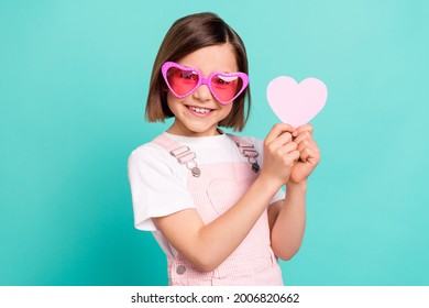 Photo of funny adorable school girl wear pink overall glasses smiling holding little heart isolated teal color background