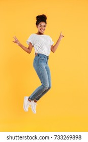 Photo of funny african joyful lady in white pullover and jeans jumping and smiling isolated