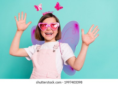 Photo of funny charming schoolgirl dressed pink overall wings dancing looking empty space isolated turquoise color background