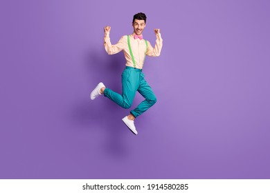 Photo of funny charming young man dressed yellow shirt jumping showing muscles isolated purple color background
