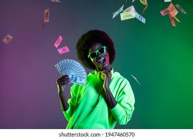 Photo of funny cool dark skin lady dressed sweatshirt eyewear arm earphones holding cash isolated neon background