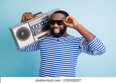 Photo of funny cool self-confident dark skin guy hold retro cassette recorder on shoulder students party chill wear sun glasses striped sailor shirt isolated blue color background