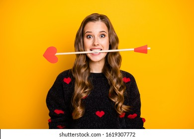 Photo of funny crazy lady work as cupid hold arrow in mouth ready to give people couples love feelings wear hearts pattern pullover isolated yellow color background