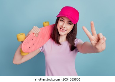 Photo of funny cute young lady wear hat holding longboard show peace v-sign isolated turquoise color background