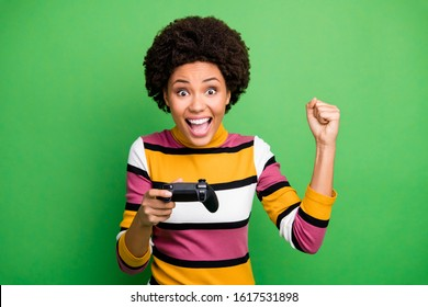 Photo of funny dark skin lady playing video games addicted gamer excited hold joystick hand celebrating winning raise fist wear casual striped sweater isolated green color background