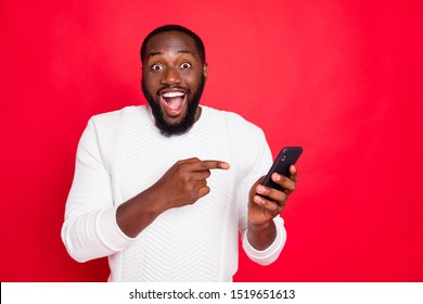 Photo of funny dark skin man holding telephone advertising new model smart phone indicating finger advice low price wear white knitted sweater isolated red background