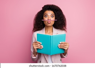 Photo of funny foolish dark skin student lady hold journal book not reading playing pen make fake mustache wear checkered blazer isolated pastel pink color background