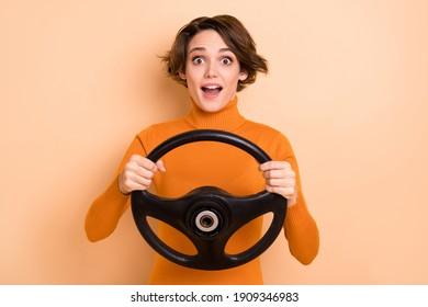 Photo of funny impressed young girl orange turtleneck holding steering wheel isolated beige color background