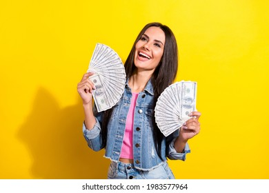 Photo of funny laughing young lady wear jeans jacket holding usd hundreds looking empty space isolated bright yellow color background