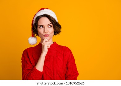 Photo of funny pretty lady celebrate winter holidays dreamy look empty space think family party hand on chin x-mas concept wear santa cap red knitted sweater isolated yellow color background