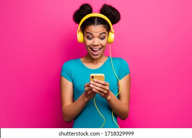 Photo of funny shocked youngster dark skin lady hold telephone hands choosing cool song playlist modern earphones wear blue casual t-shirt isolated bright pink color background