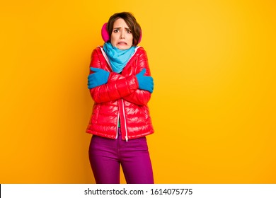Photo of funny traveler lady not expect frosty weather shaking hug herself wear stylish casual short red overcoat blue scarf gloves ear warmers pants isolated yellow color background