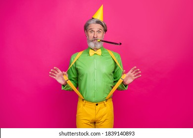 Photo of funny white haired grandpa hold yellow suspenders blow noisemaker funky crazy birthday party surprise wear paper cap green shirt pants isolated bright pink color background