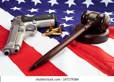 Photo of gavel, gun, and bullets over an american flag.