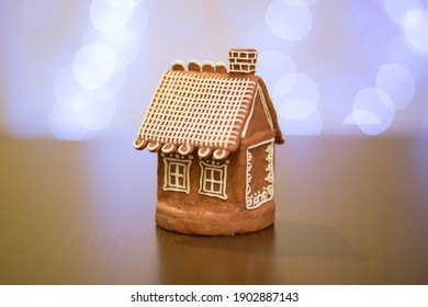 Photo with a gingerbread house standing on a wooden table, with a glowing garland in the background. - Shutterstock ID 1902887143