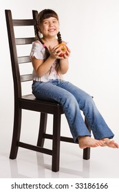 Photo of a girl with apple, sitting on a chair