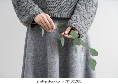 Photo of a girl in a gray knitted pullover and a skirt on the light gray background in the studio. She holds an eucalyptus branch in the hands. Closeup. Horizontal.