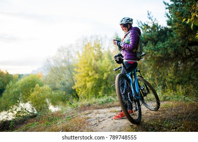 Photo of girl in helmet standing with phone in hands near bicycle