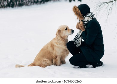 Photo of girl with labrador on walk in winter park