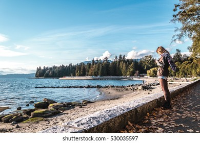 Photo of Girl Looking at her Phone near Stanley Park in Vancouver, Canada