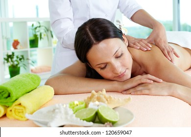 Photo of a girl lying on the massage table, massage therapist doing the procedure