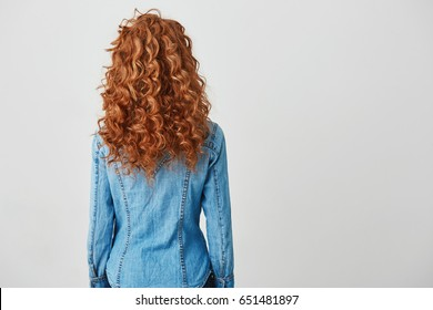 Photo of girl with red curly hair standing back to camera over white background. Copy space.